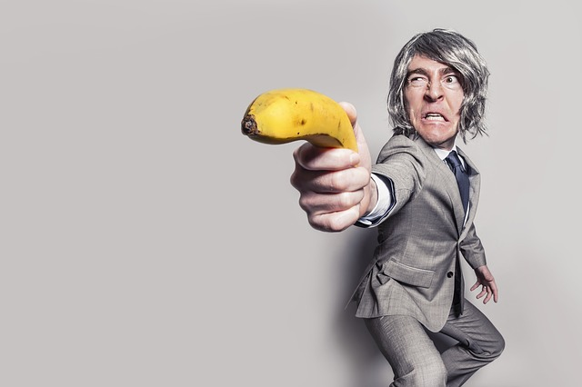 Muž v obleku a s parochňou na hlave miery pred seba banánom.jpg