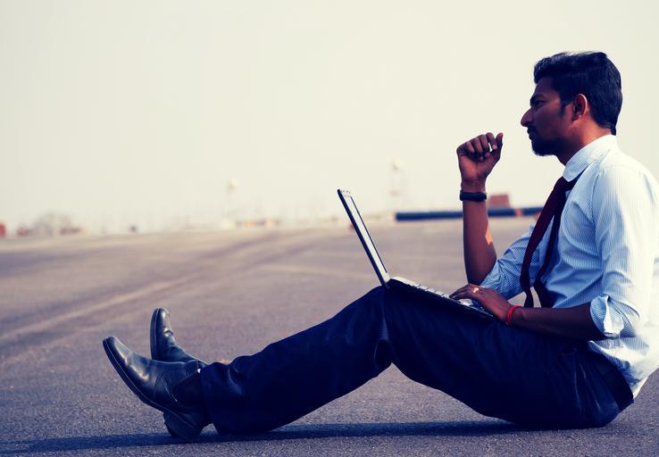 Muž, podnikateľ sedí na ceste, premýšľa a pracuje s notebookom.jpg