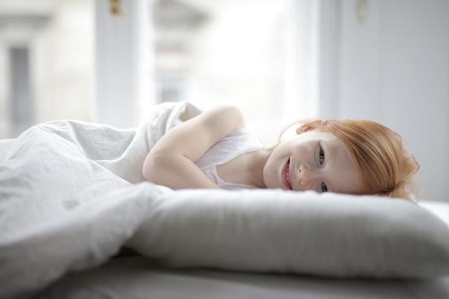 Usmiate dievča leží na posteli